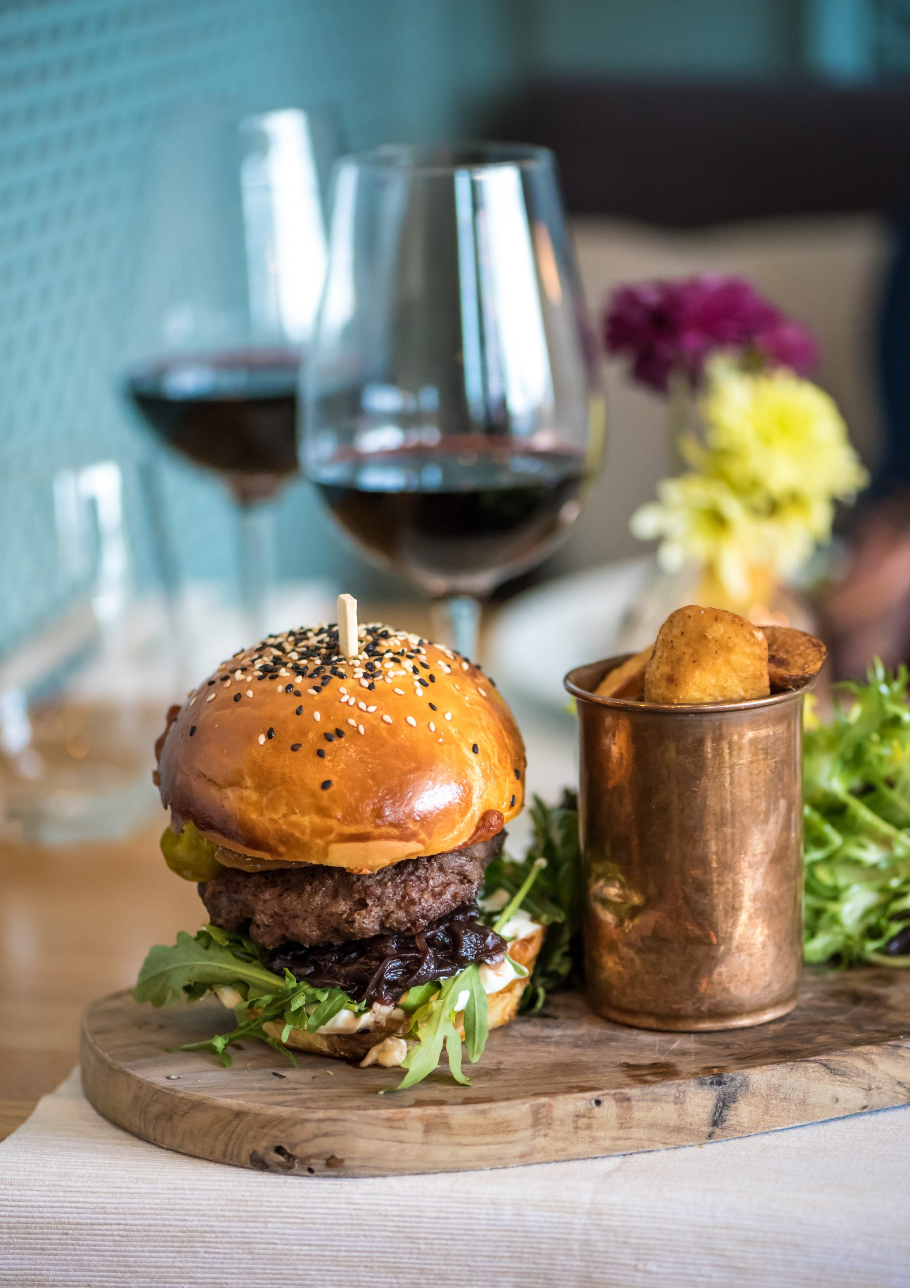 An american beef burger with fried potatoes and red wine